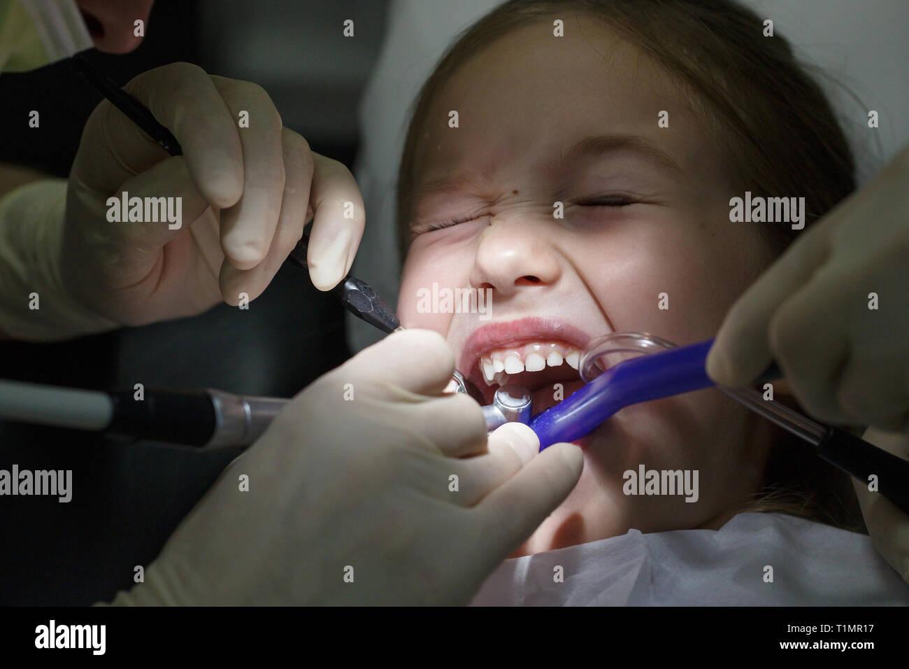Peur petite fille à l'office, les dentistes dans la douleur lors d'un examen de santé. Les soins dentaires pédiatriques et la peur du dentiste concept. Banque D'Images