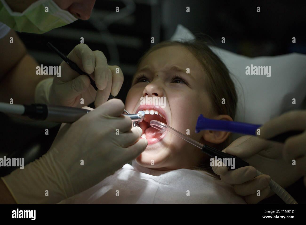 Peur petite fille à l'office, les dentistes dans la douleur lors d'un traitement. Les soins dentaires pédiatriques et la peur du dentiste concept. Banque D'Images