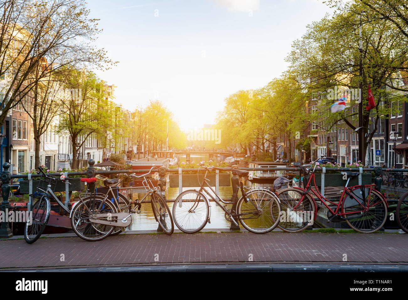 Plus de vélo de ville Amsterdam canal en Pays-bas avec vue sur la rivière Amstel, au coucher du soleil. Banque D'Images