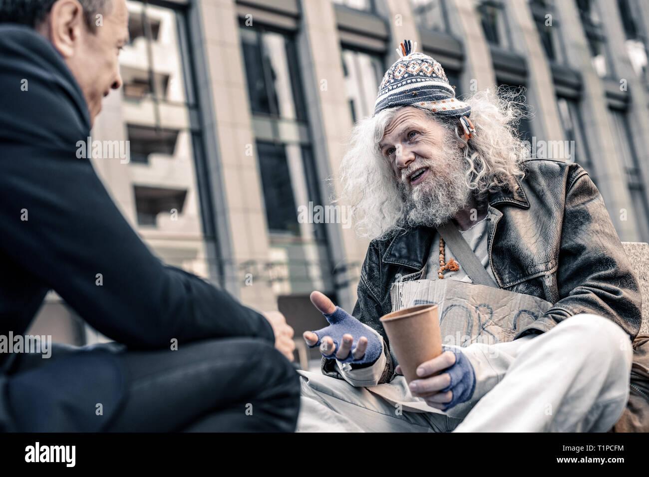 Reconnaissant le pauvre homme aux cheveux long main tremblante de piétons généreux Photo Stock