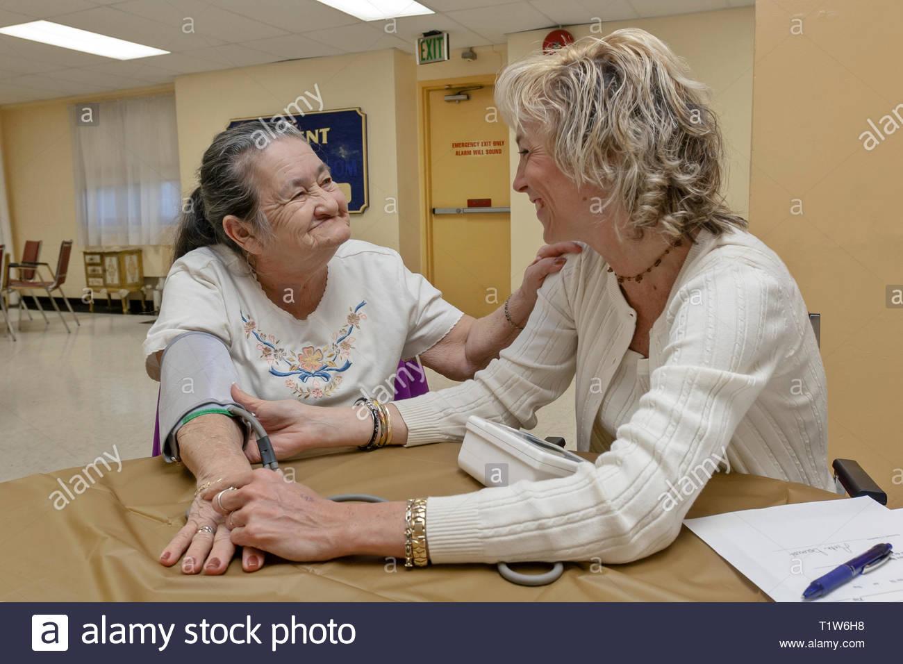 Une infirmière prend la pression artérielle d'une femme senior dans un programme d'approche communautaire. Banque D'Images