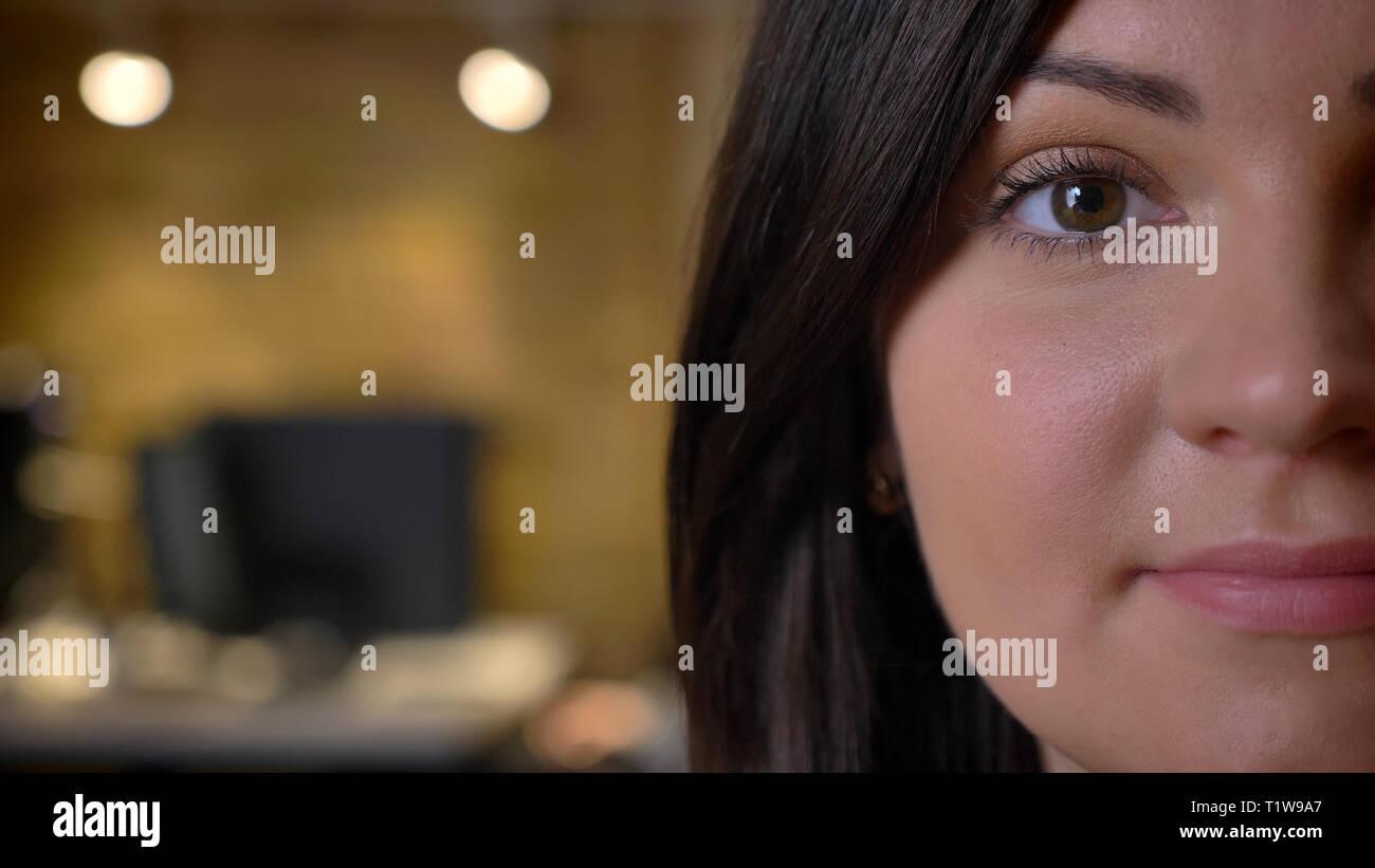 Close-up demi-portrait de belle femme d'âge moyen surpoids regarder calmement en huis clos sur fond de bureau. Photo Stock
