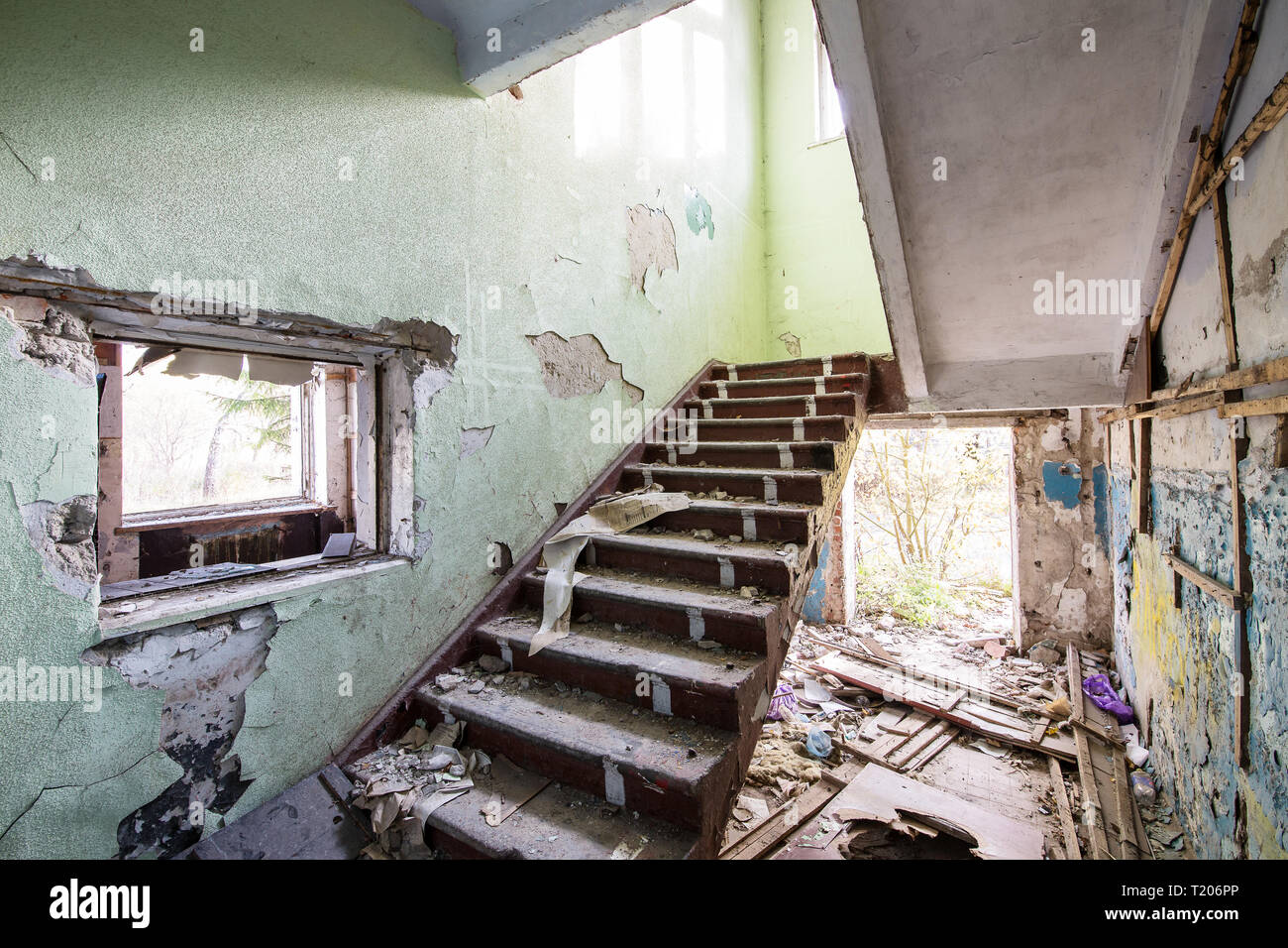 Escalier en béton dans la vieille maison en ruine abandonnée sur une journée ensoleillée Banque D'Images