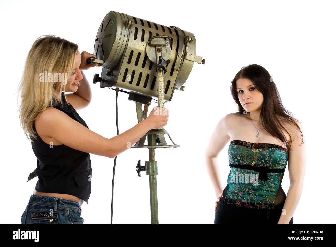 Un assistant photo illumine un modèle. La technique d'éclairage est périmée. Isolé sur un fond blanc. Photo Stock