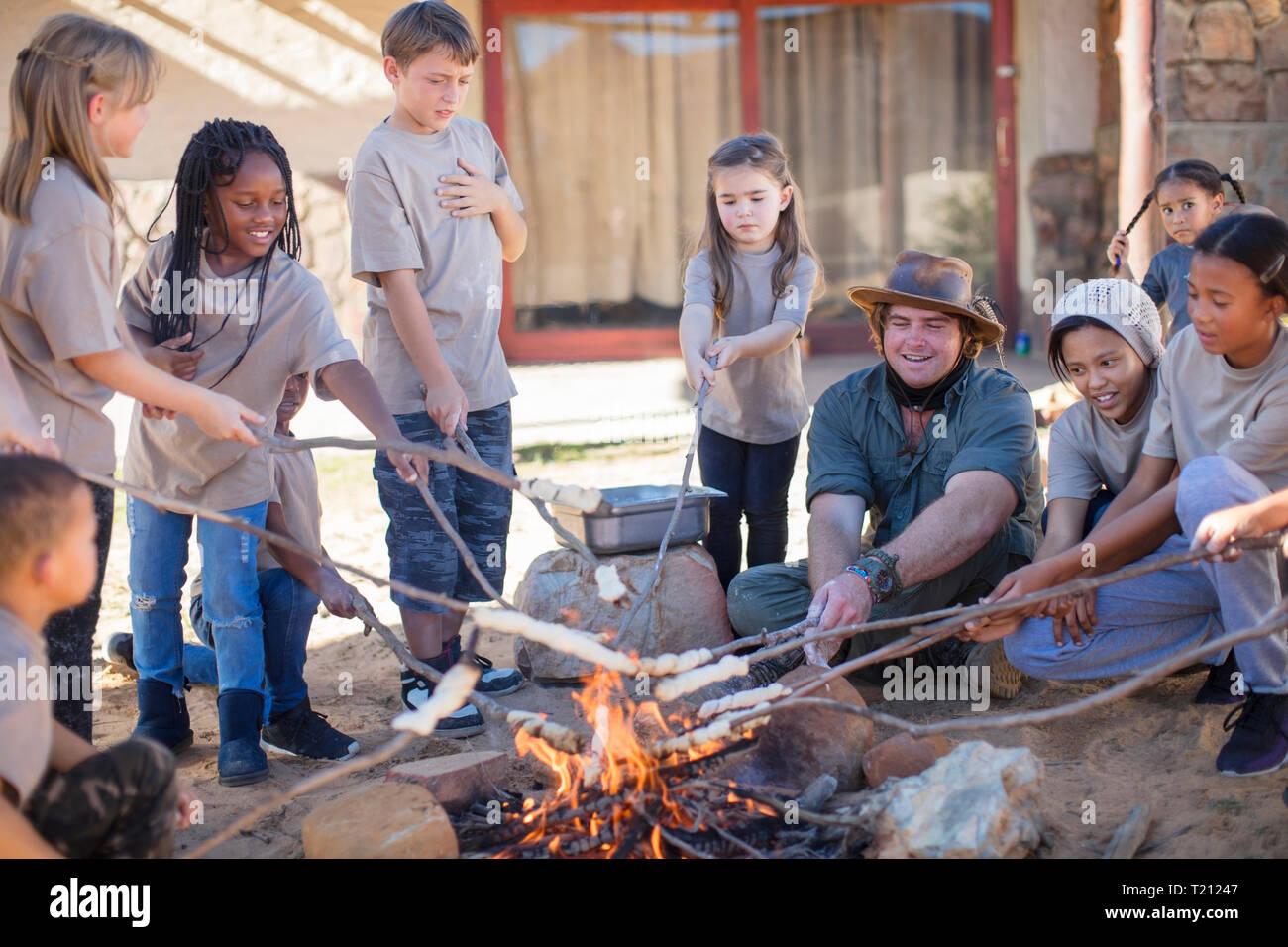 Les enfants et le grillage du pain à torsion guide de feu de camp Photo Stock