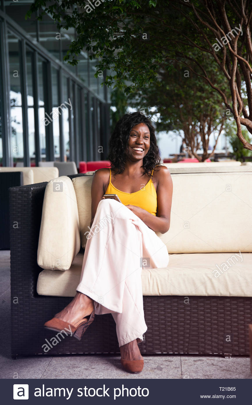 Une femme afro-brésilien, assis dans un salon de jardin à Rio de Janeiro, Brésil Photo Stock