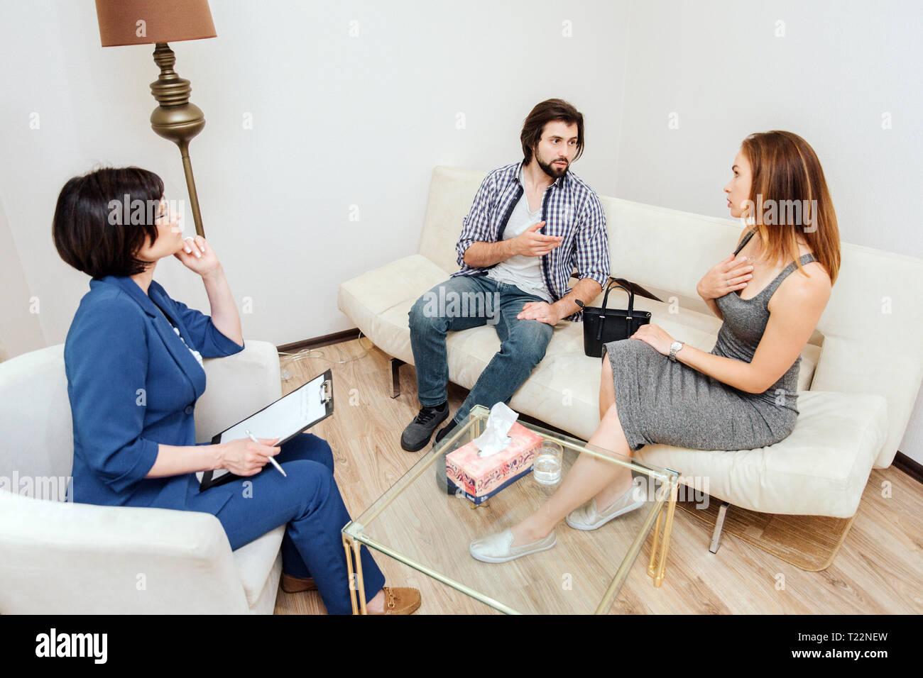 Couplt est assis et parler les uns avec les autres. L'homme est orienté sur la femme. Elle est orientée onn herselfDoctor est à leur écoute très prudent. Photo Stock
