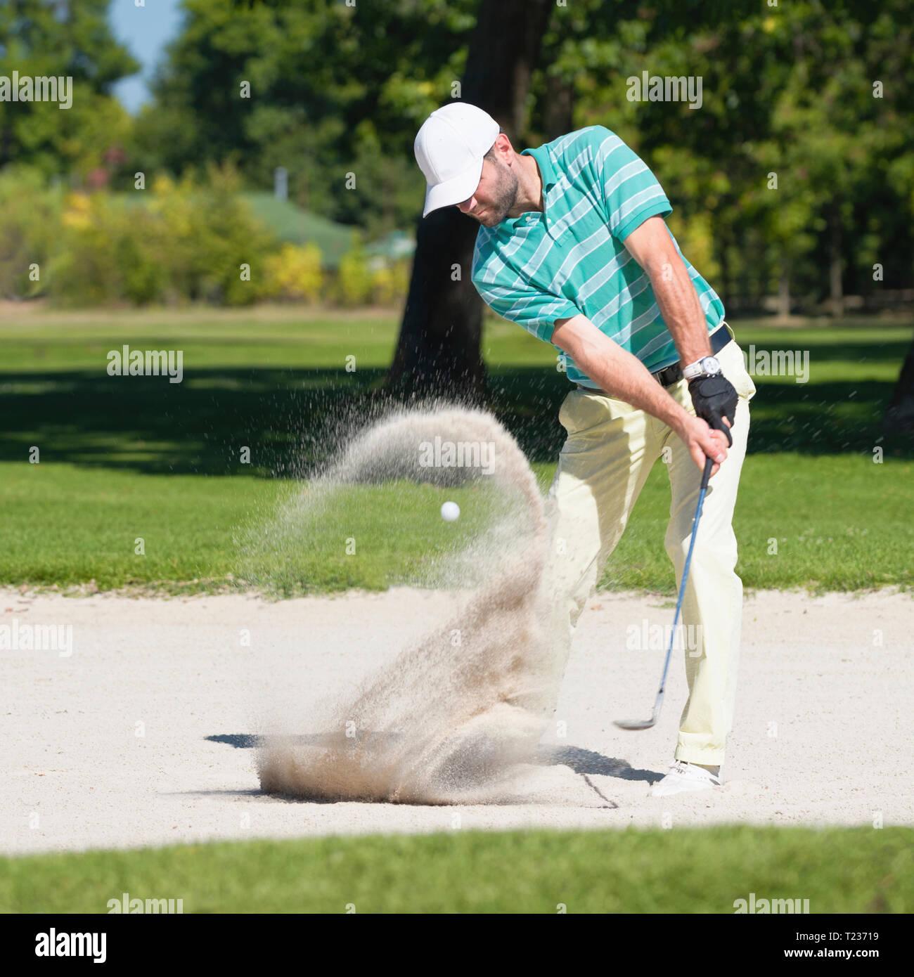 Golfeur frappe la balle hors de fosse de sable. L'accent sur golfeur, boule de sable dans la vague de flou. Banque D'Images