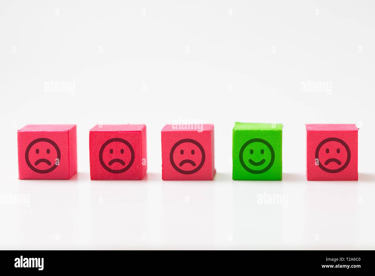 Unique, optimiste, bonheur, différence concept en utilisant seul visage heureux entre de nombreux visages tristes. Photo Stock