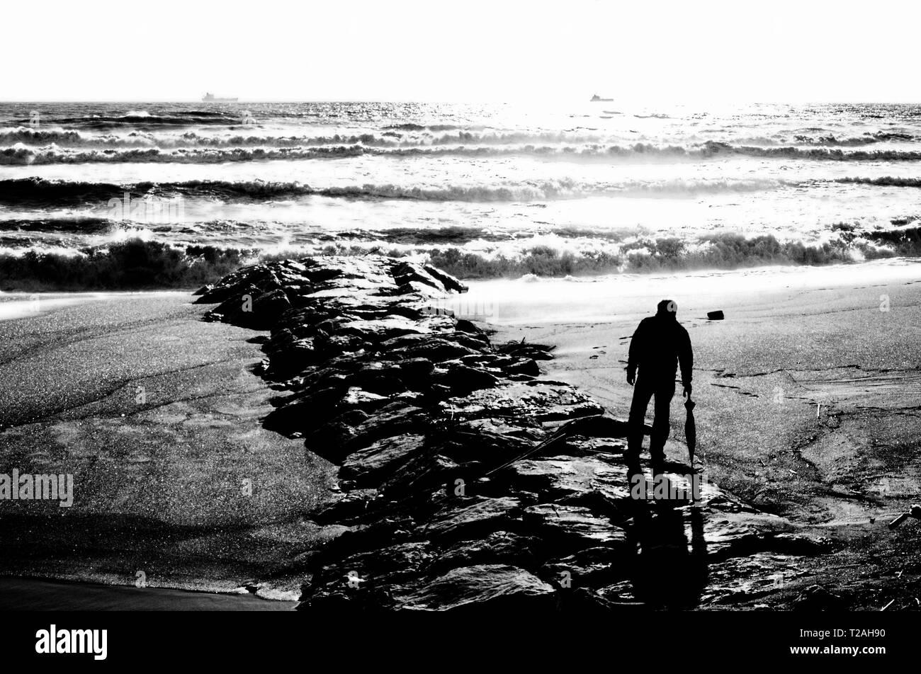 Un homme sur la plage regarde l'état de la mer Photo Stock