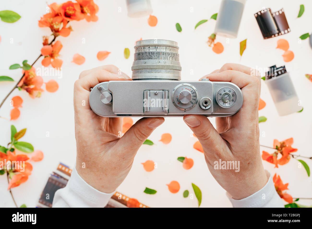 Woman holding vintage camera sur la décoration florale de printemps, la saison du printemps est idéal pour commencer un nouveau passe-temps comme la photographie Photo Stock