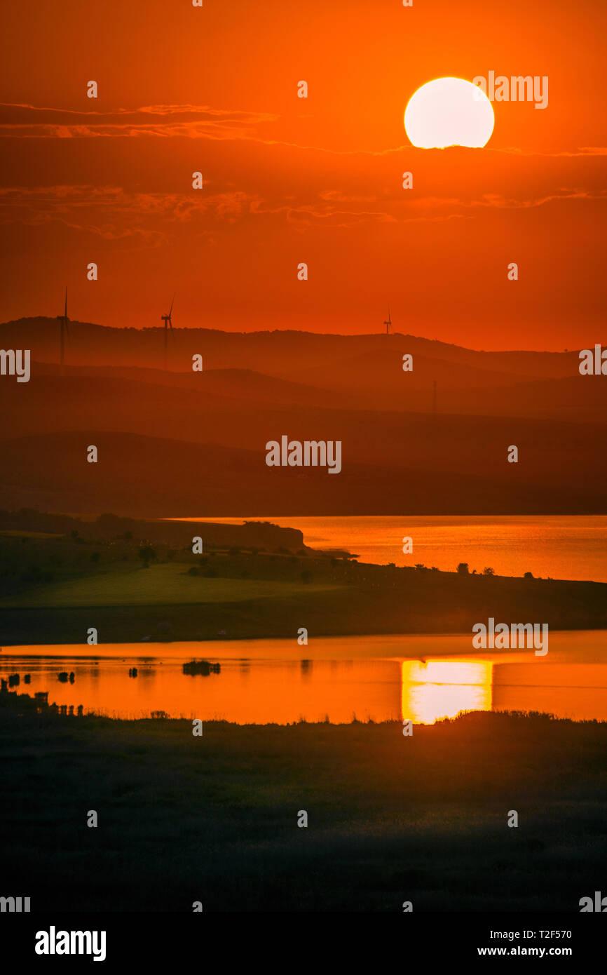 Éoliennes éoliennes placées sur des collines utilisée pour produire de l'électricité verte écologique tourné au coucher du soleil avec un lac au premier plan des couleurs riches et éclatantes Banque D'Images