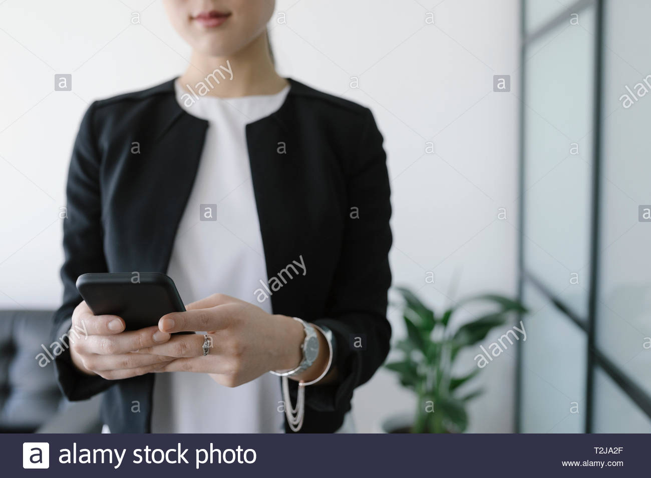 Businesswoman using smart phone in office Photo Stock