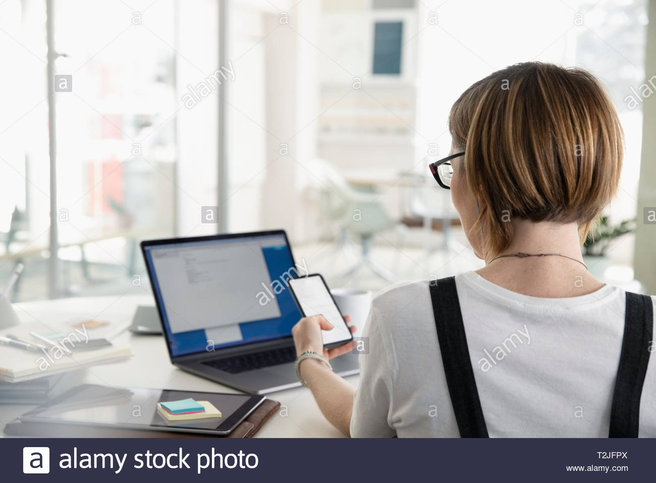 Businesswoman using smart phone at desk in office Photo Stock