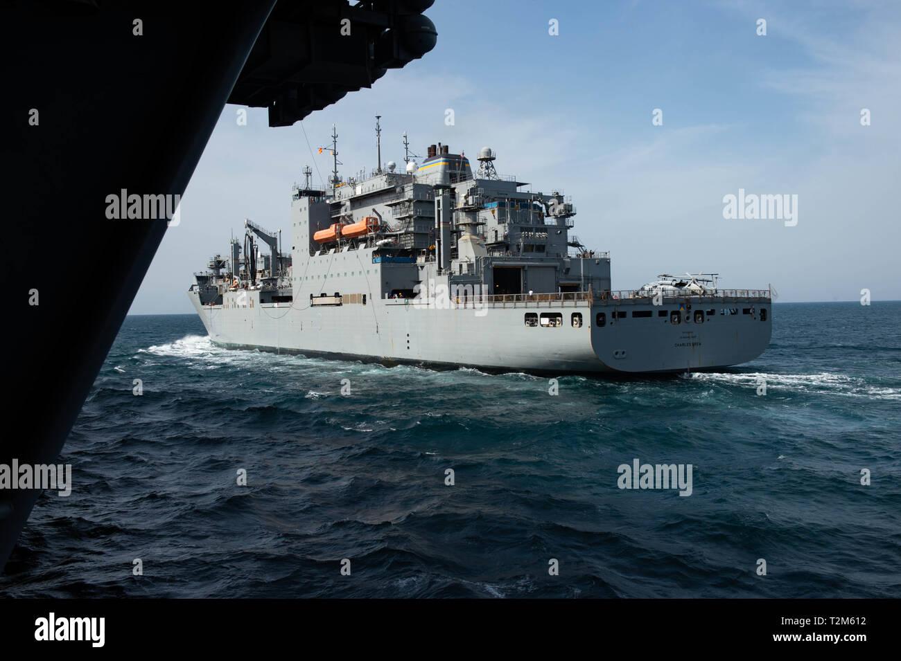 Les cargaisons sèches et de munitions ship USNS Charles Drew (T-AKE 10) cuit avec le porte-avions USS JOHN C. STENNIS (CVN 74) au cours d'un ravitaillement en mer dans le Golfe Arabe, le 28 mars 2019. Le John C. Stennis dans le groupe est déployé pour la 5e flotte américaine zone d'opérations à l'appui des opérations navales pour assurer la stabilité et la sécurité maritime dans la région Centrale, reliant la Méditerranée et le Pacifique à travers l'ouest de l'Océan indien et trois points d'étranglement stratégiques. (U.S. Photo par marine Spécialiste de la communication de masse Seaman Apprentice Jordanie Ripley) Photo Stock