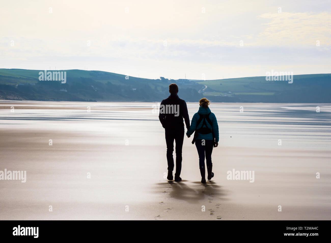 Un couple marchant ensemble sur une paisible plage de sable à marée basse. Woolacombe, North Devon, England, UK, Grande-Bretagne Photo Stock