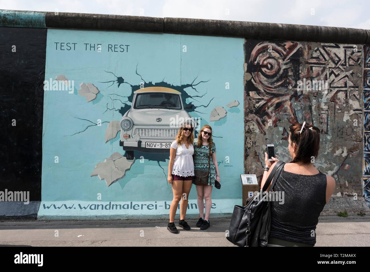 Berlin. L'Allemagne. Les touristes posent pour des photos en face de Birgit Kinder's célèbre peinture murale 'Tester le reste' sur le mur de Berlin à l'East Side Gallery. Banque D'Images