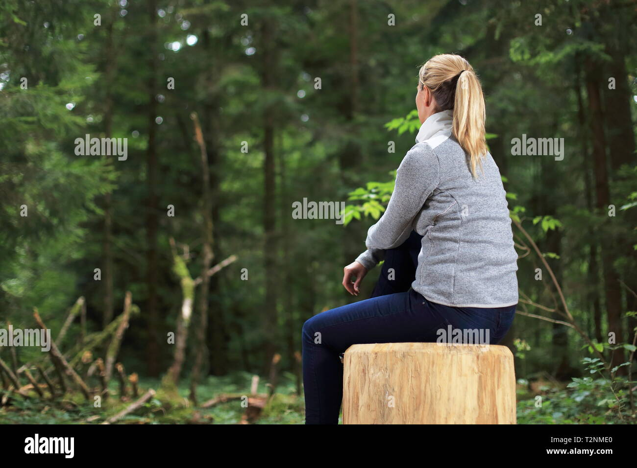 Une femme détendue sur un tronc d'arbre dans une forêt Photo Stock