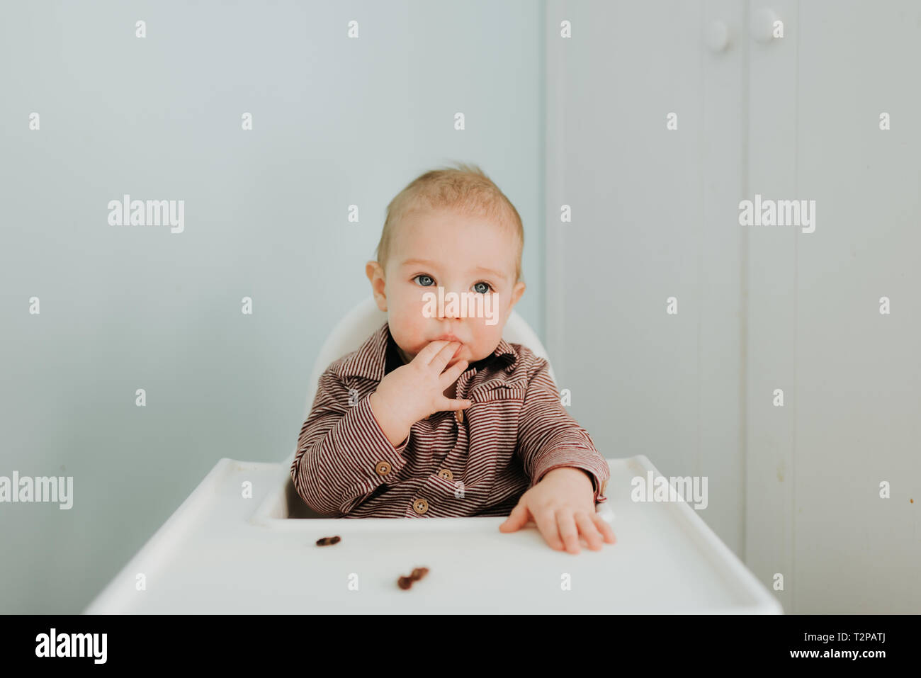 Bébé garçon dans une chaise haute, portrait Banque D'Images