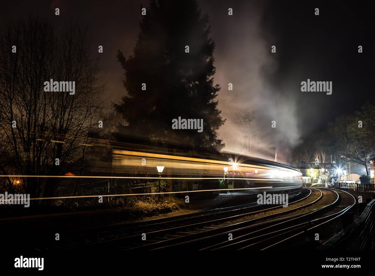 Train à vapeur et voitures qui se déplacent dans l'atmosphère et traversent la gare d'époque la nuit dans l'obscurité. Flou de mouvement rapide. Vitesse de concept. Banque D'Images