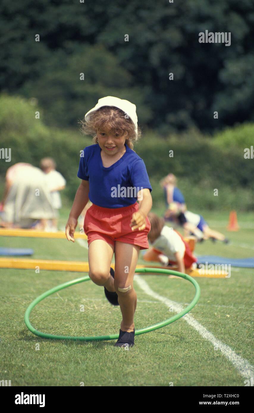 La course d'obstacles en écolière primaire à l'école sports le jour Photo Stock