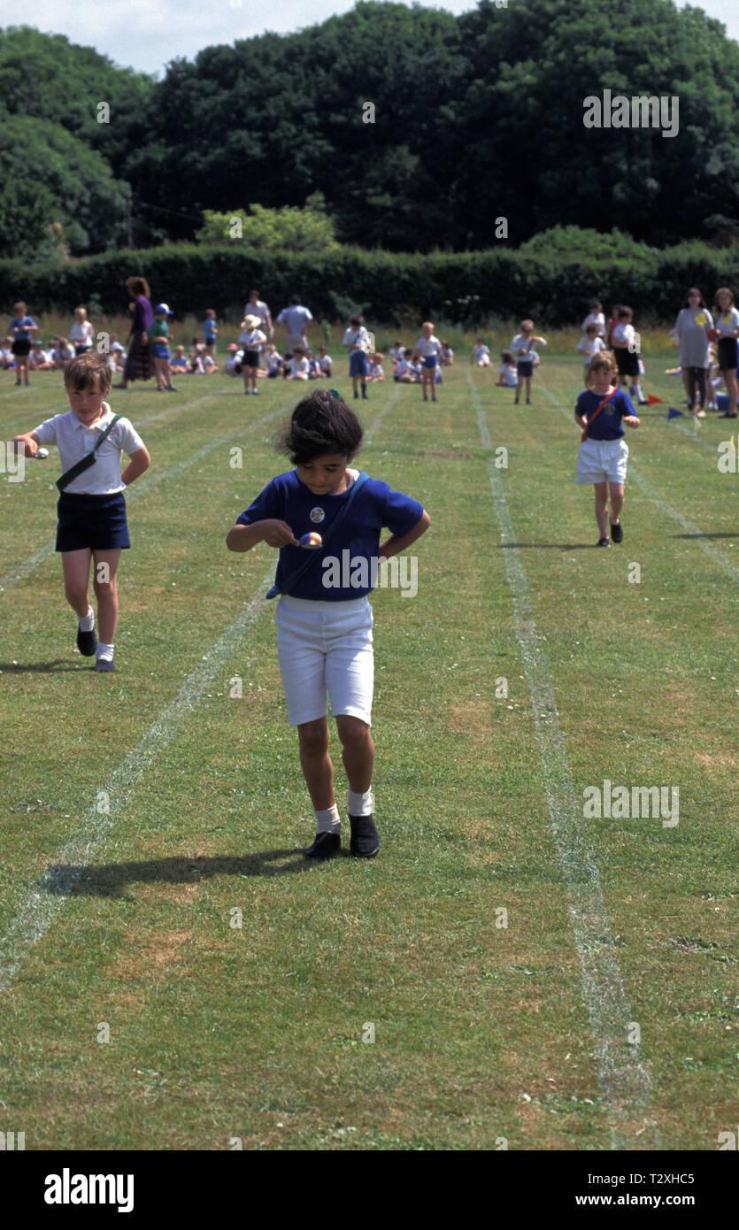 Fille de l'école primaire dans l'oeuf et la cuillère course pendant la journée des sports Photo Stock