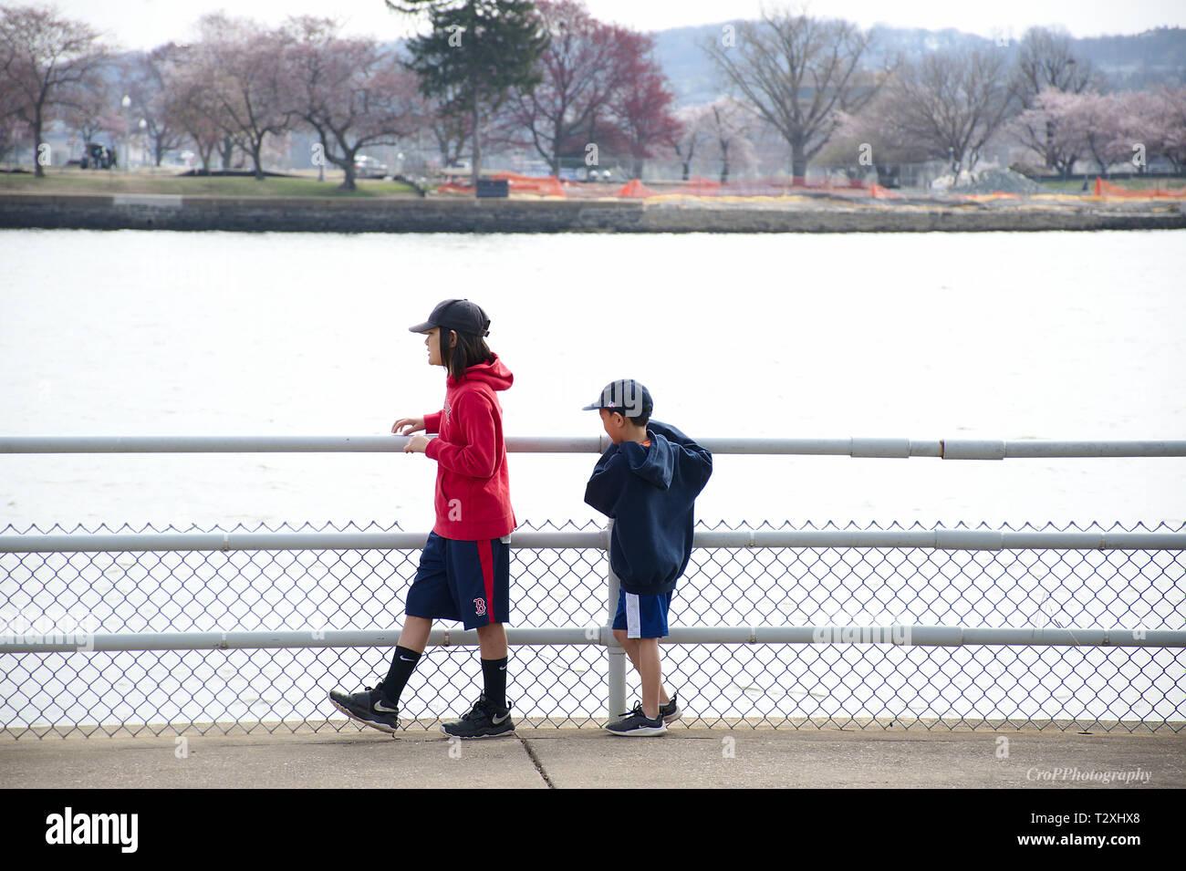 Deux jeunes qui se promenaient dans balustrade près de l'eau Photo Stock
