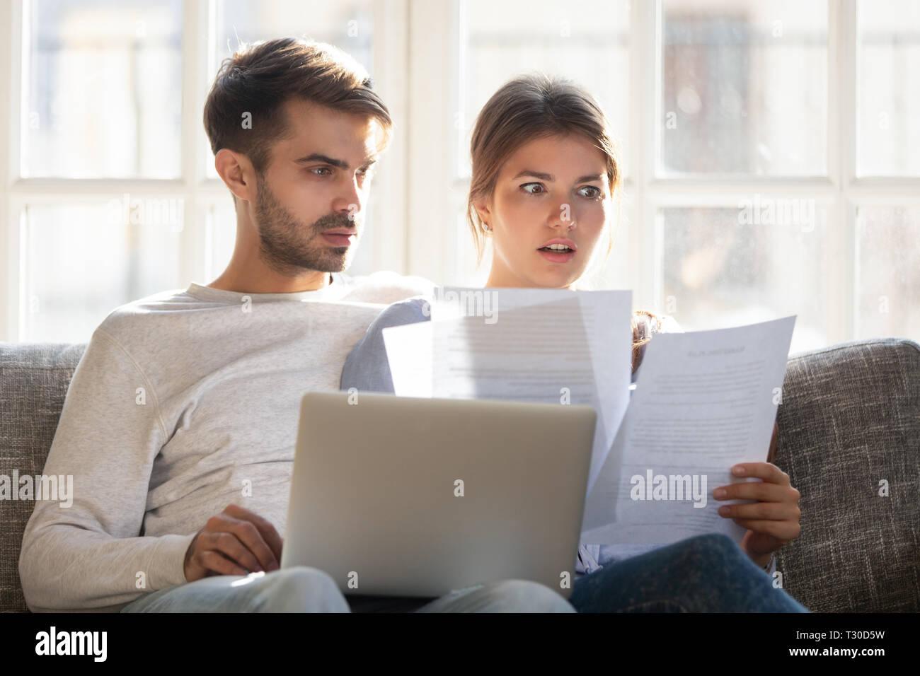 Choqué par les mauvaises nouvelles couple sitting on couch reading lettre Banque D'Images