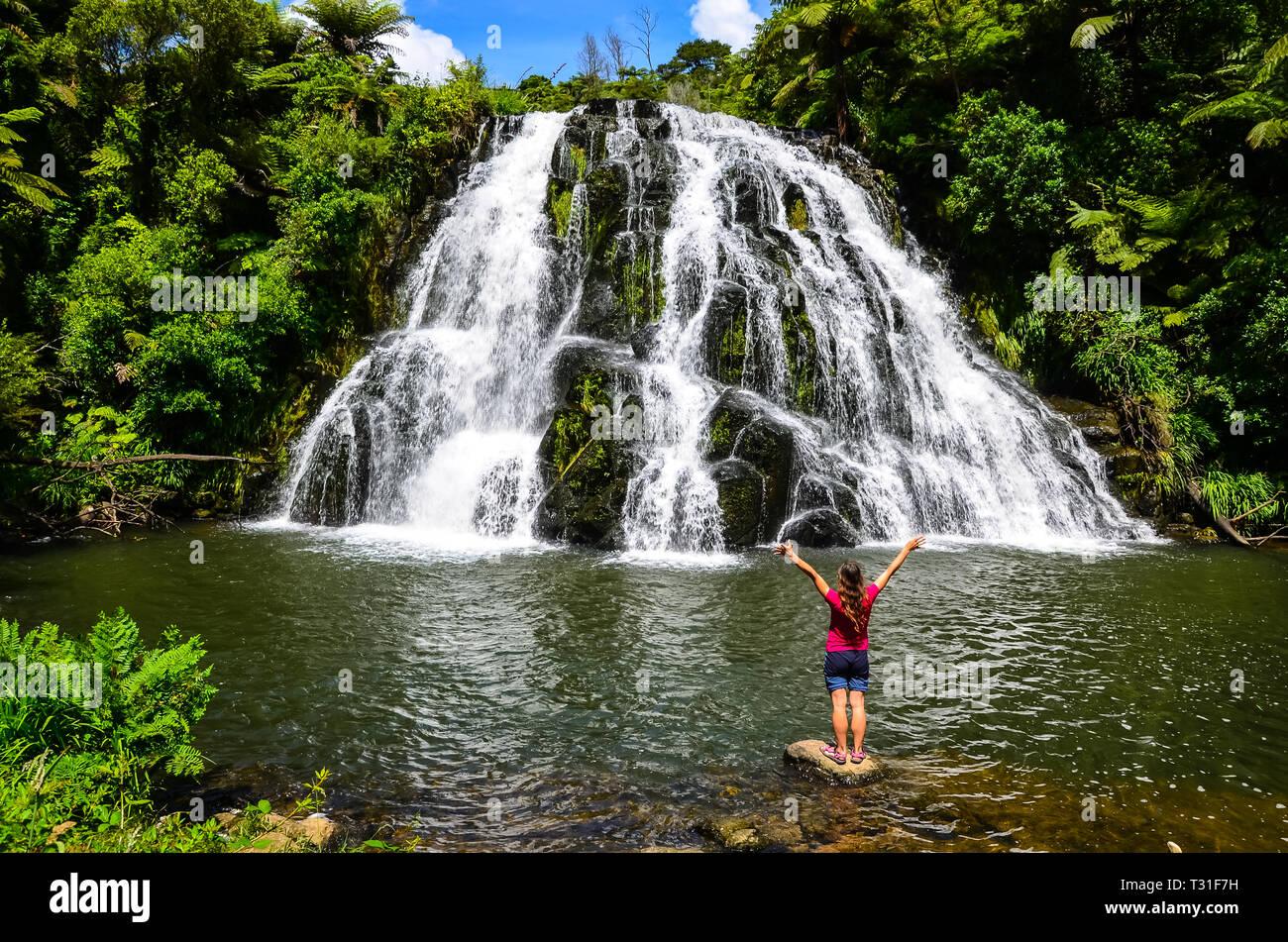 Owharoa Falls avec ciel bleu au-dessus et en personne touristiques fille t-shirt rouge à l'avant-plan à la péninsule de Coromandel, île du Nord, Nouvelle-Zélande Photo Stock