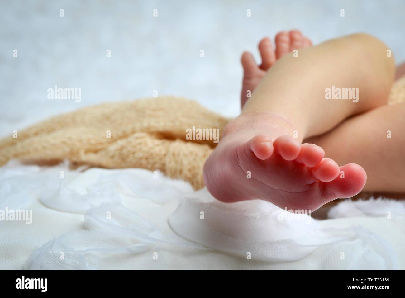 Un portrait Portrait d'un bébé nouveau-né des pieds et les pieds dans l'environnement de couleur neutre et blanc Banque D'Images
