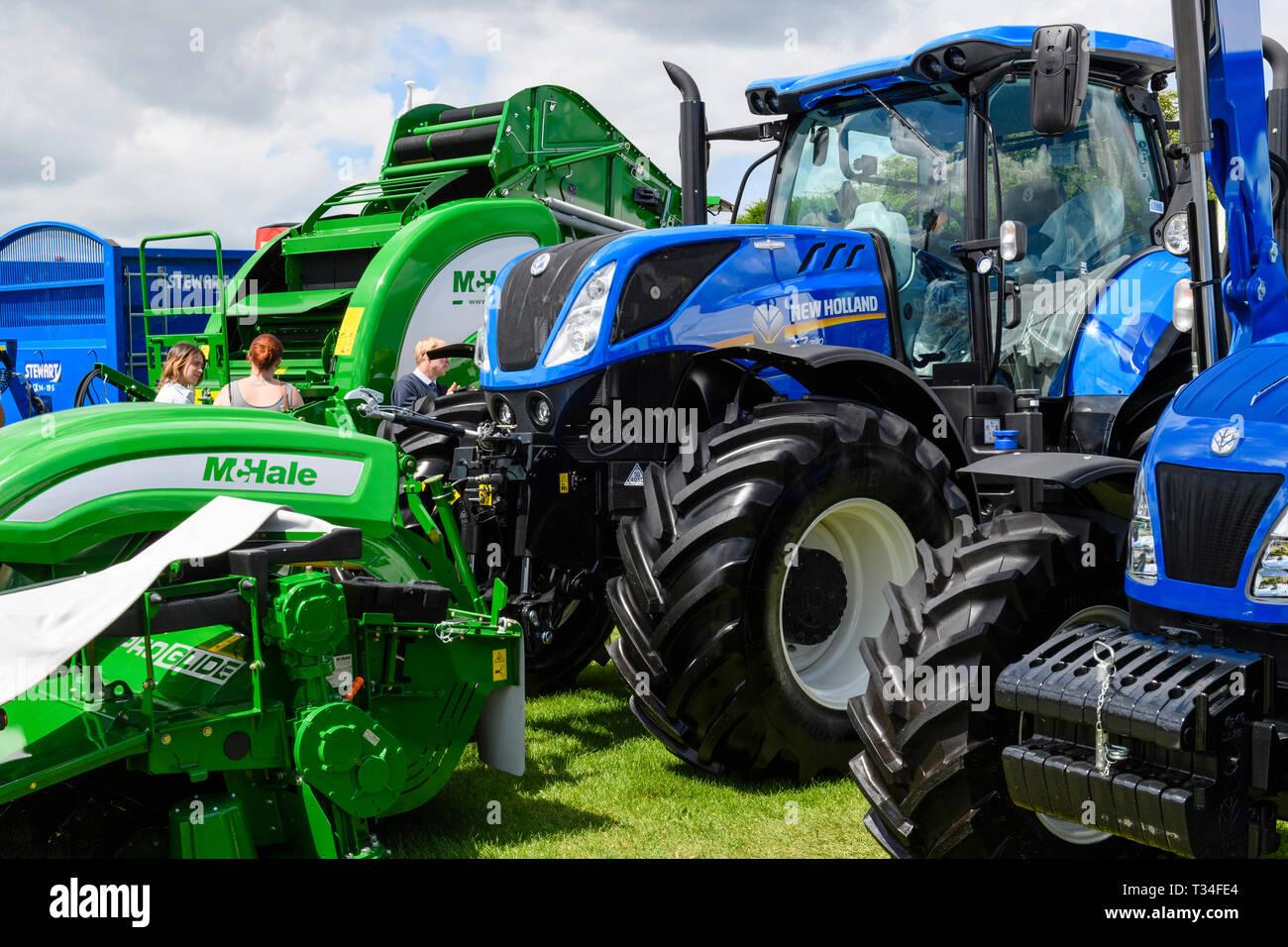 Affichage des machines agricoles (tracteurs New Holland, McHale ramasseuse-presse & tondeuse) garés côte à côte sur le commerce stand - Great Yorkshire Show, England, UK. Banque D'Images
