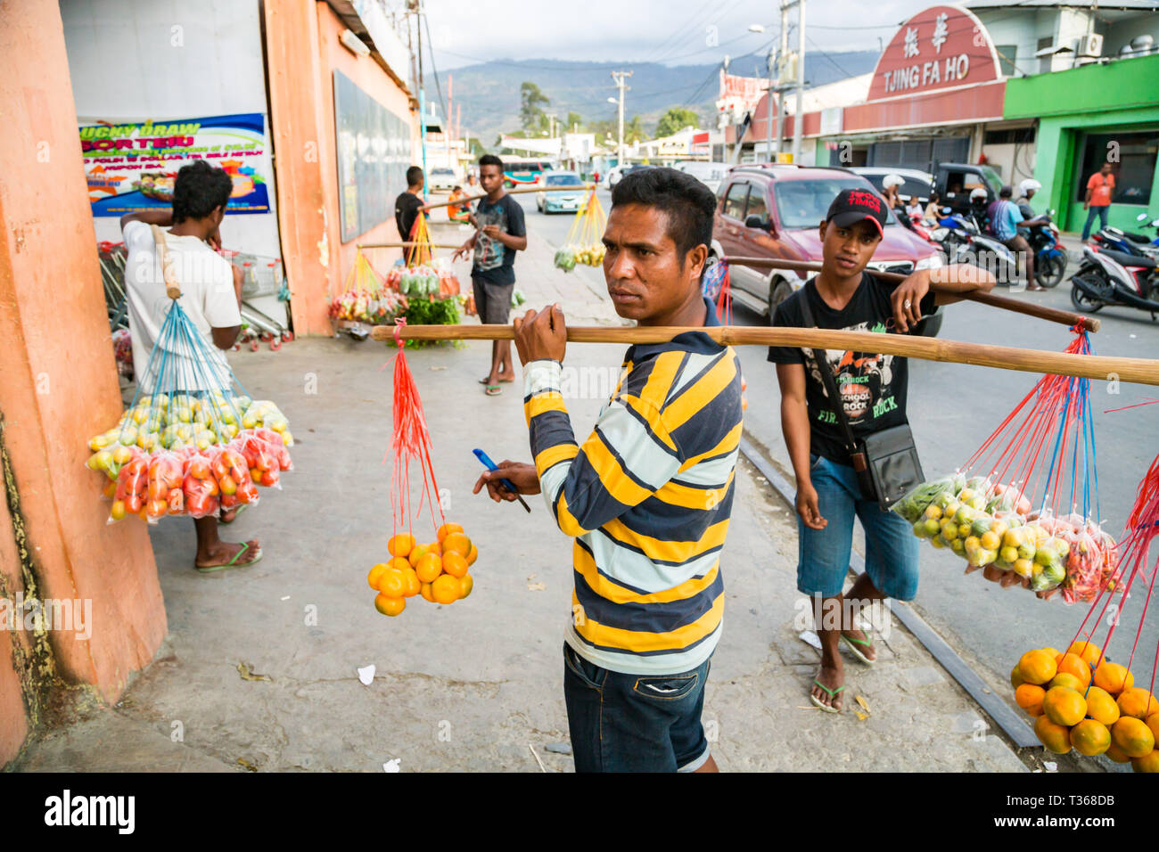 Les hommes, les Timorais de rue les fruits et légumes sur des cordes suspendues au cou de jougs faites de bâtons sur un marché très fréquenté de la rue capitale Dili, Timor oriental. Banque D'Images