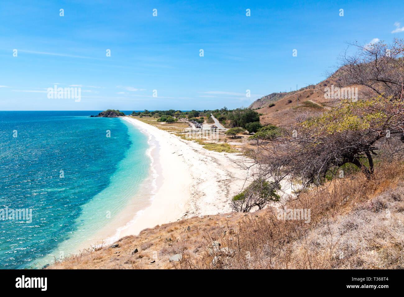 L'un dollar beach. Plage de sable jaune Idillic du Timor oriental, au Timor-Leste. Littoral avec des collines, des montagnes et la savane sèche. Paysage rural et la nature b Banque D'Images
