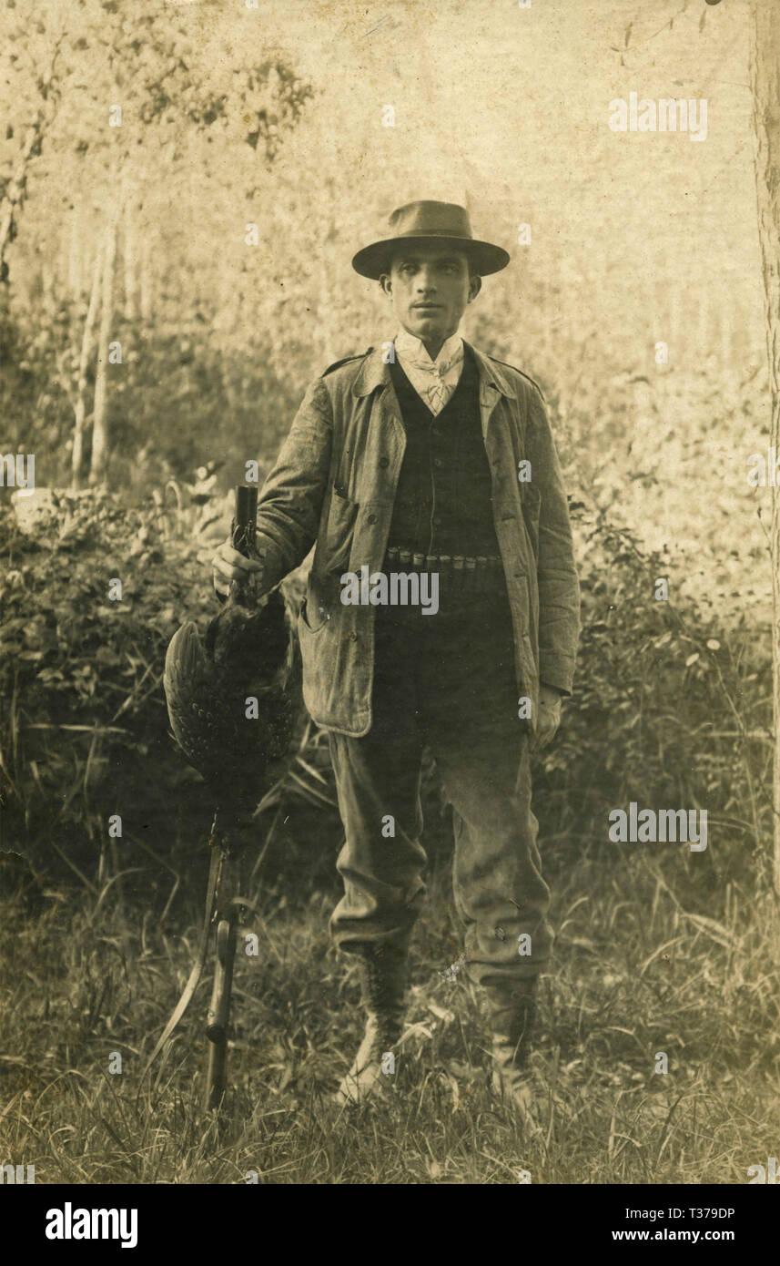 Hunter posant avec son fusil et prier, l'Italie des années 1900 Photo Stock