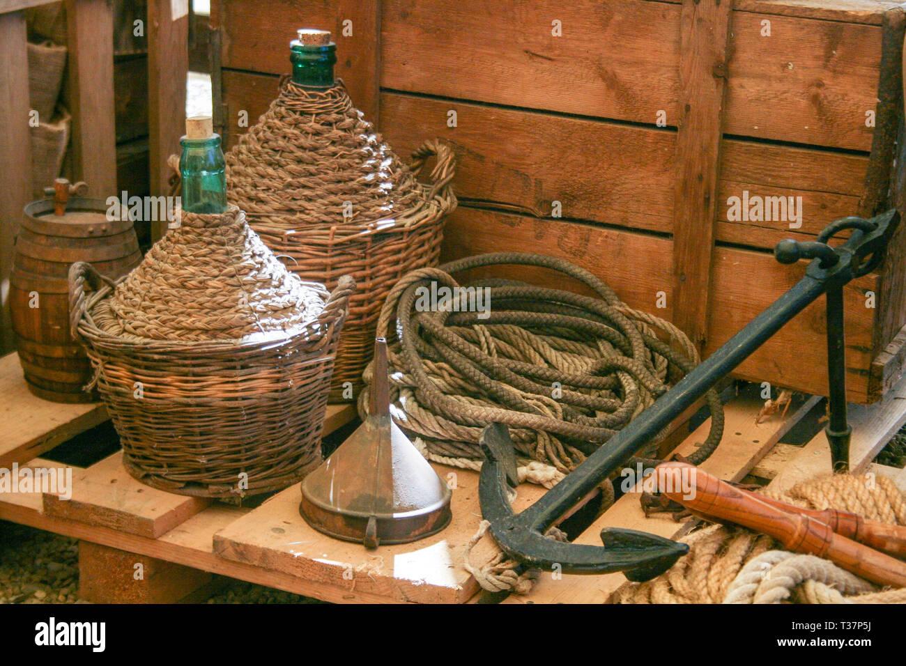 La composition avec ancienne en bois panier et de vin vieux flacons avec corde et l'ancre en Italie Photo Stock