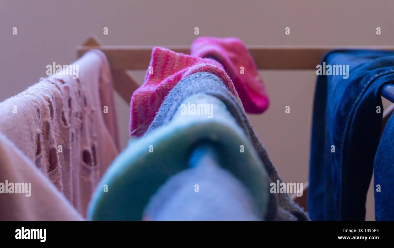 Se concentrer sur une chaussette rose le séchage sur un étendoir à linge avec d'autres vetements femme, chaussettes dépareillées et floues dans l'avant-plan. Dépeignant laundry day. Photo Stock