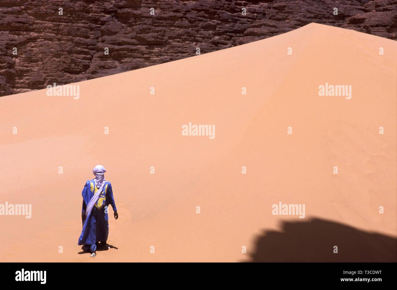 Homme touareg dans un costume traditionnel, marcher sur une dune, l'Algérie Photo Stock