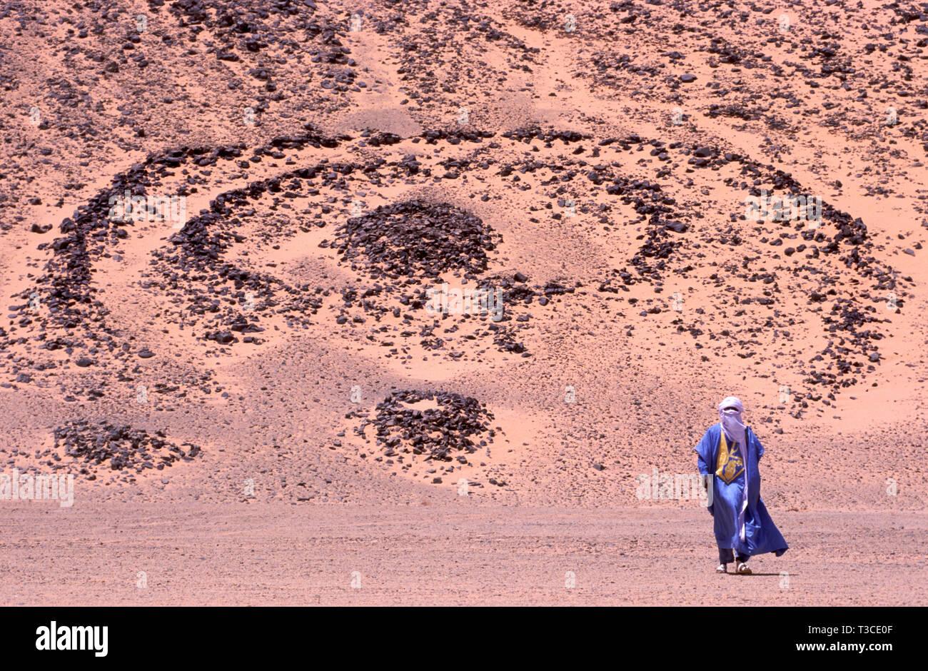 Homme touareg dans un costume traditionnel, avec une année 5000 vieille tombe en arrière-plan dans le Sahara en Algérie Photo Stock