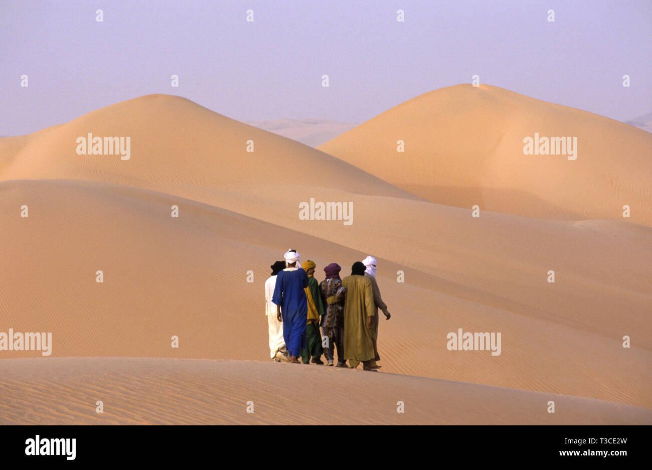 Groupe d'hommes touareg randonnée à travers le désert du Sahara, l'Algérie Photo Stock