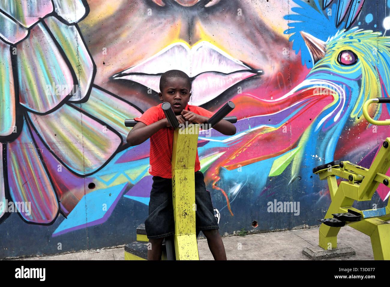 Jeune garçon sur une machine d'exercice en plein air devant une murale colorée dans la Comuna 13, Medellin, Colombie Photo Stock