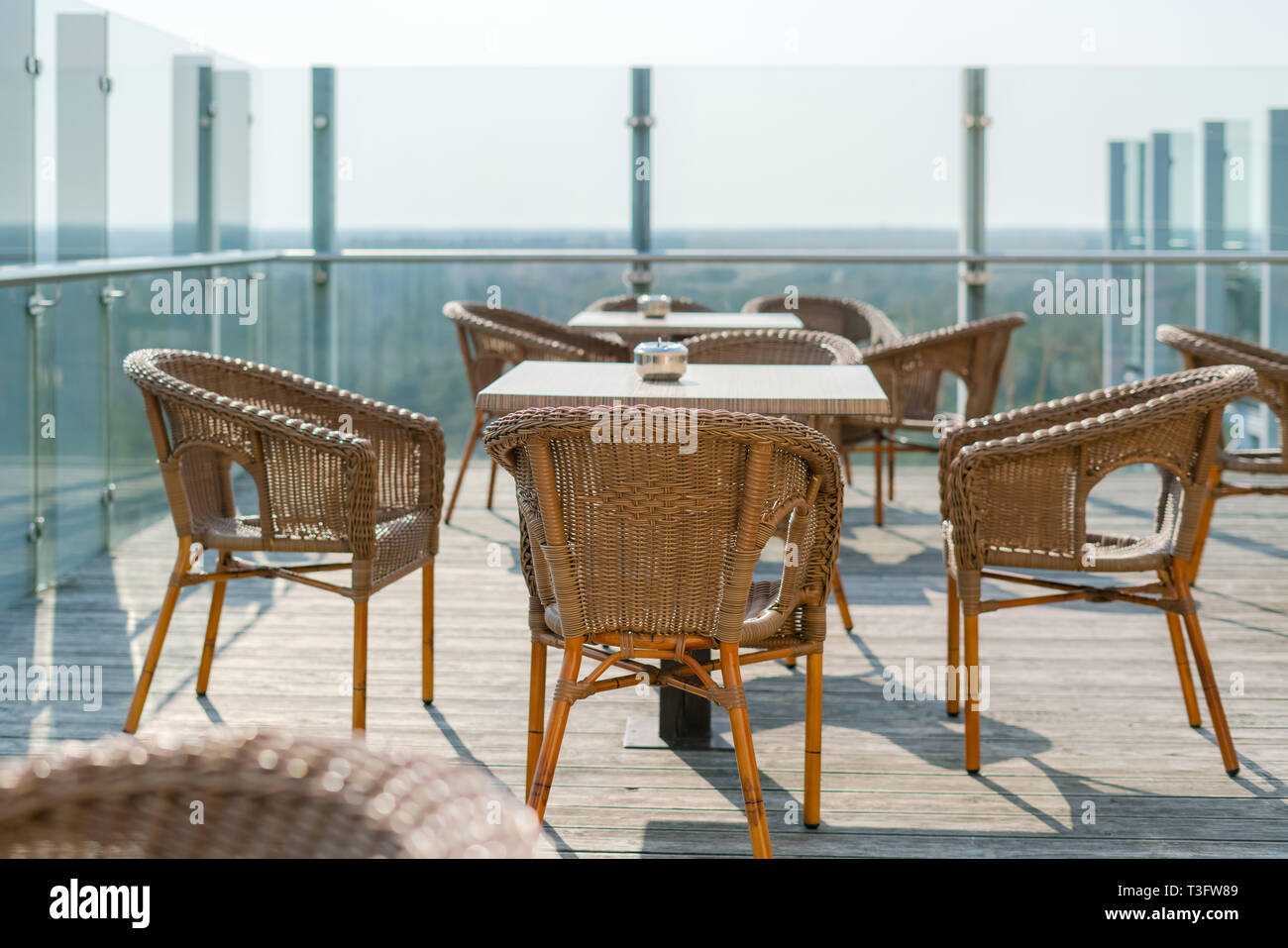Café vide avec des fauteuils en osier et en rotin tables sur jardin ...