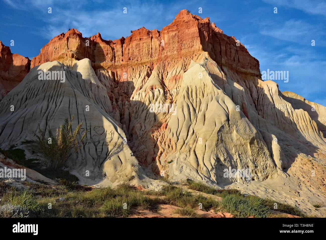 Gougé falaises rouges et blanches qui forment une toile de fond de l'étendue de sable sans fin sur la plage Praia da Falesia, Albuferia, Algarve, Portugal, Europe. Banque D'Images