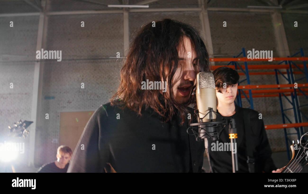 Un groupe de rock ayant une répétition. Le Chant soliste Photo Stock
