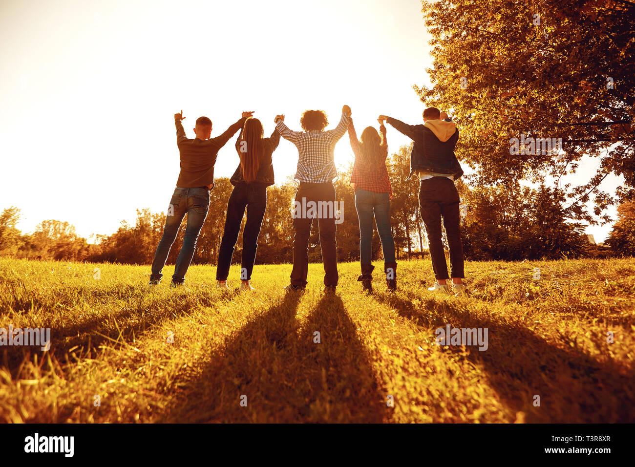 Personnes debout avec les bras levés on meadow Banque D'Images