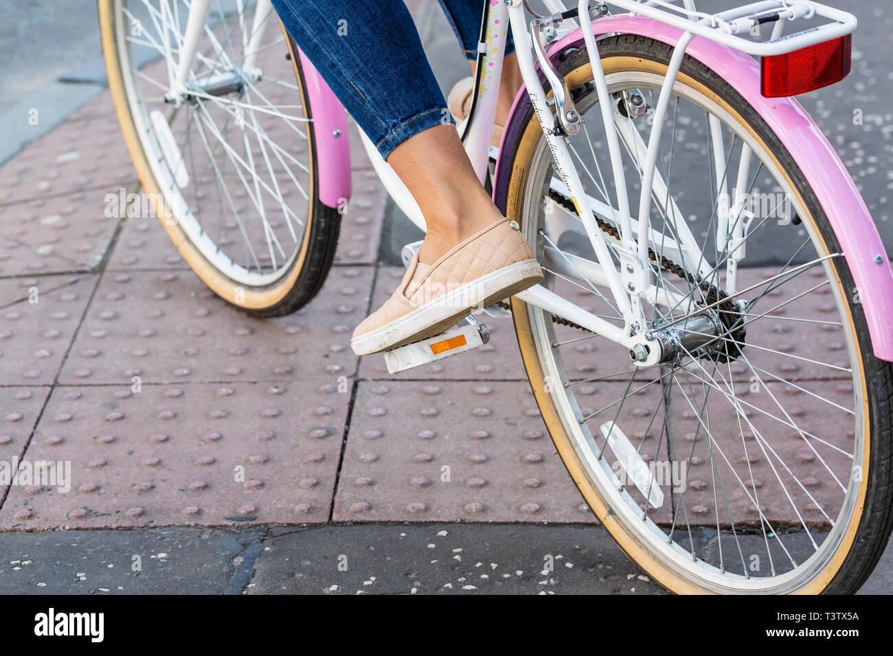 Partie inférieure d'une femme sur un vélo Photo Stock