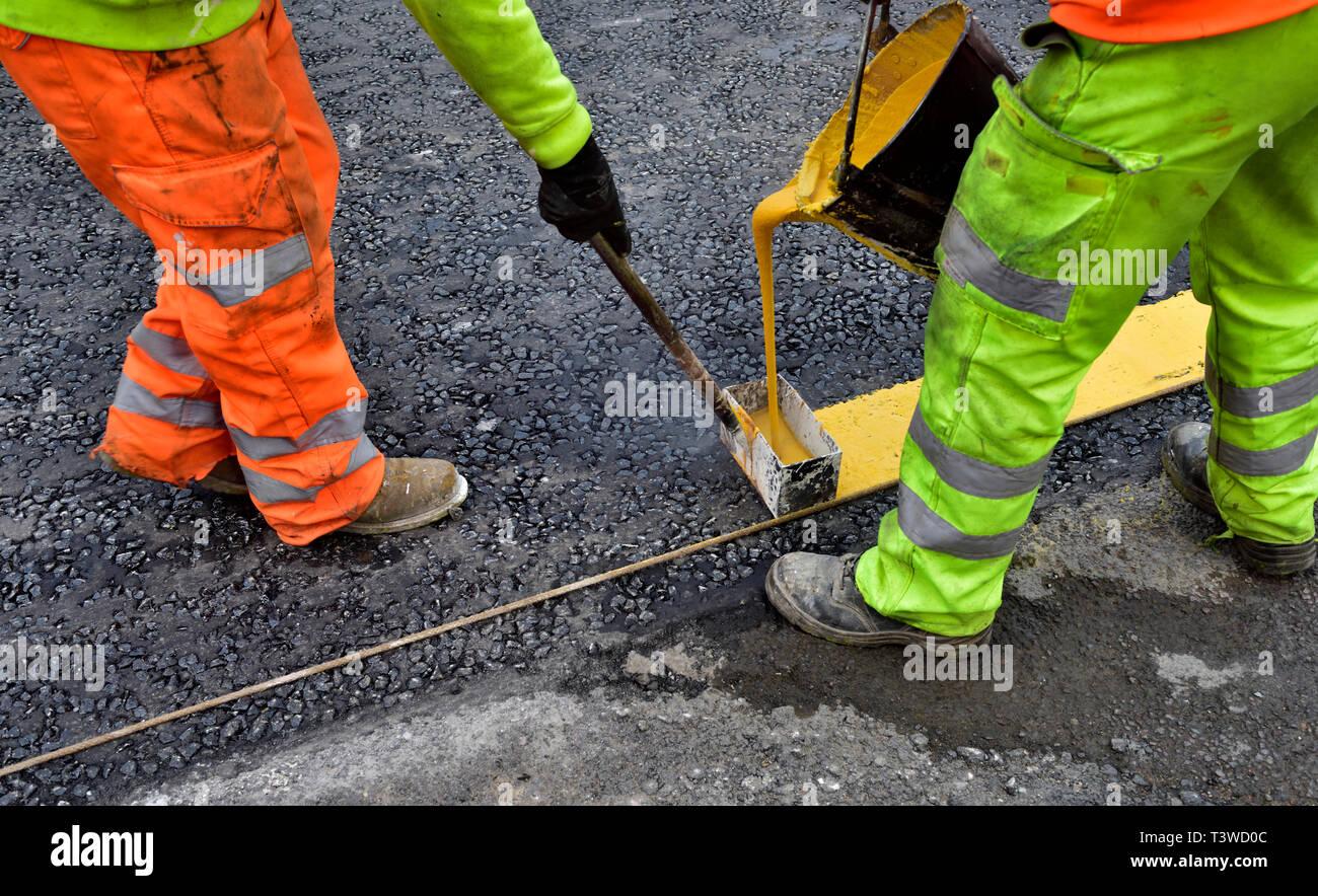 Workman mise en route jaune avec marquage peinture hot melt Photo Stock