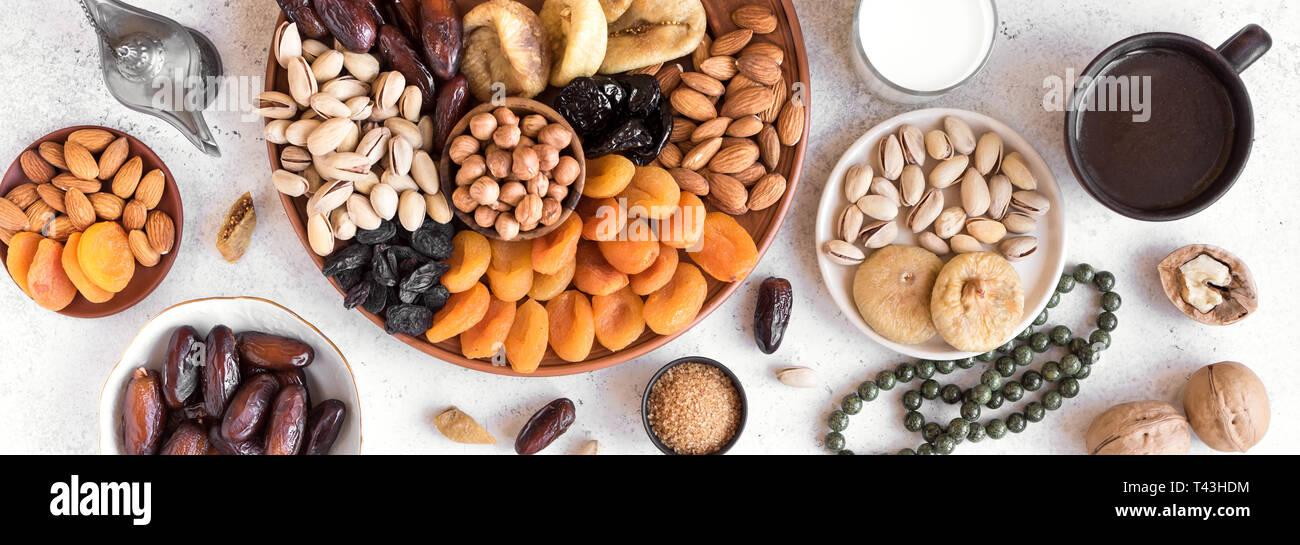 L'Iftar musulmanes traditionnelles de nourriture, l'espace de copie. Ramadan kareem avec dates premium,noix, fruits secs, de café et de lait, la bannière. Banque D'Images