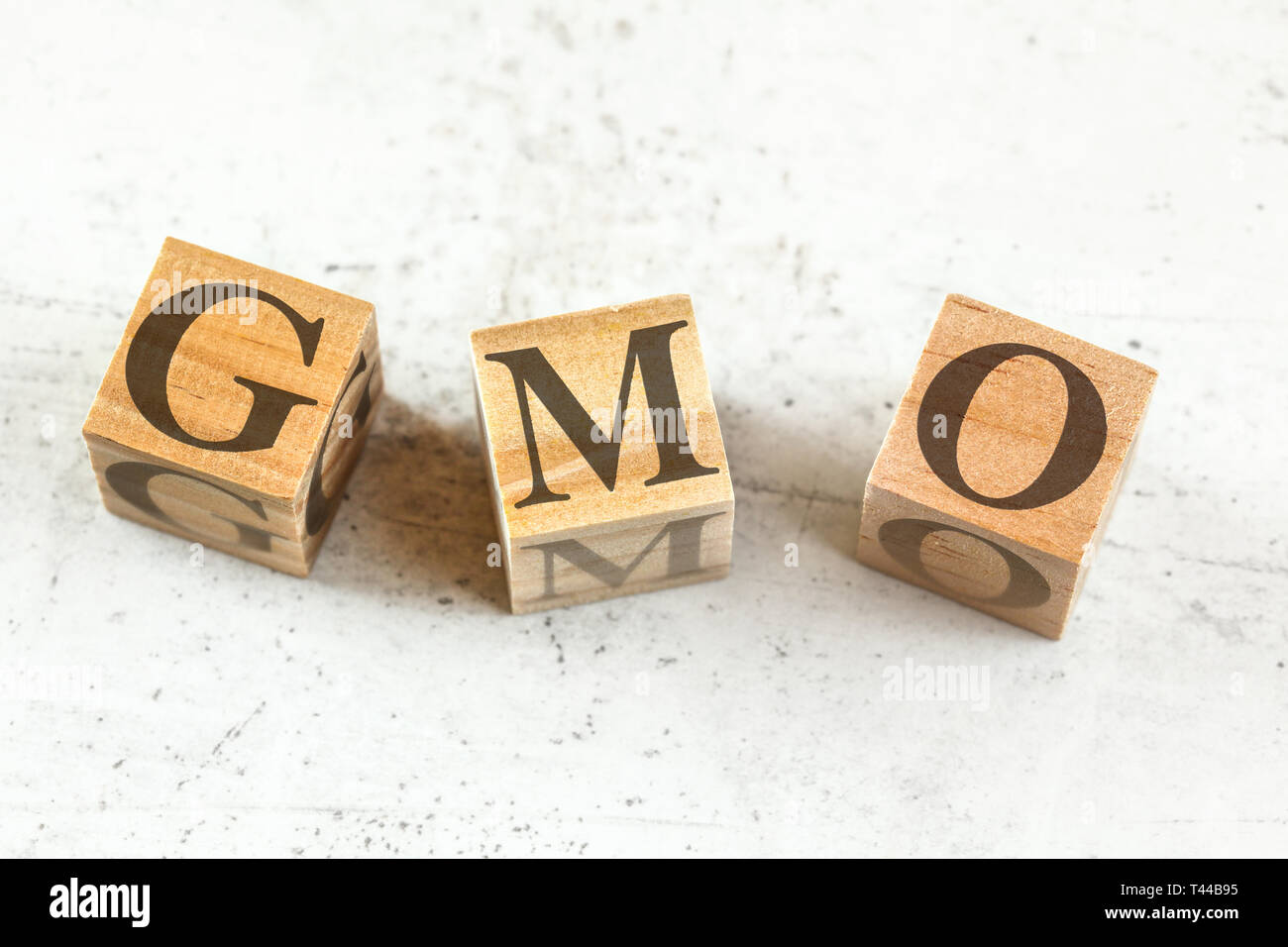 Trois cubes en bois avec des lettres pour les OGM organisme génétiquement modifié sur un tableau blanc. Photo Stock