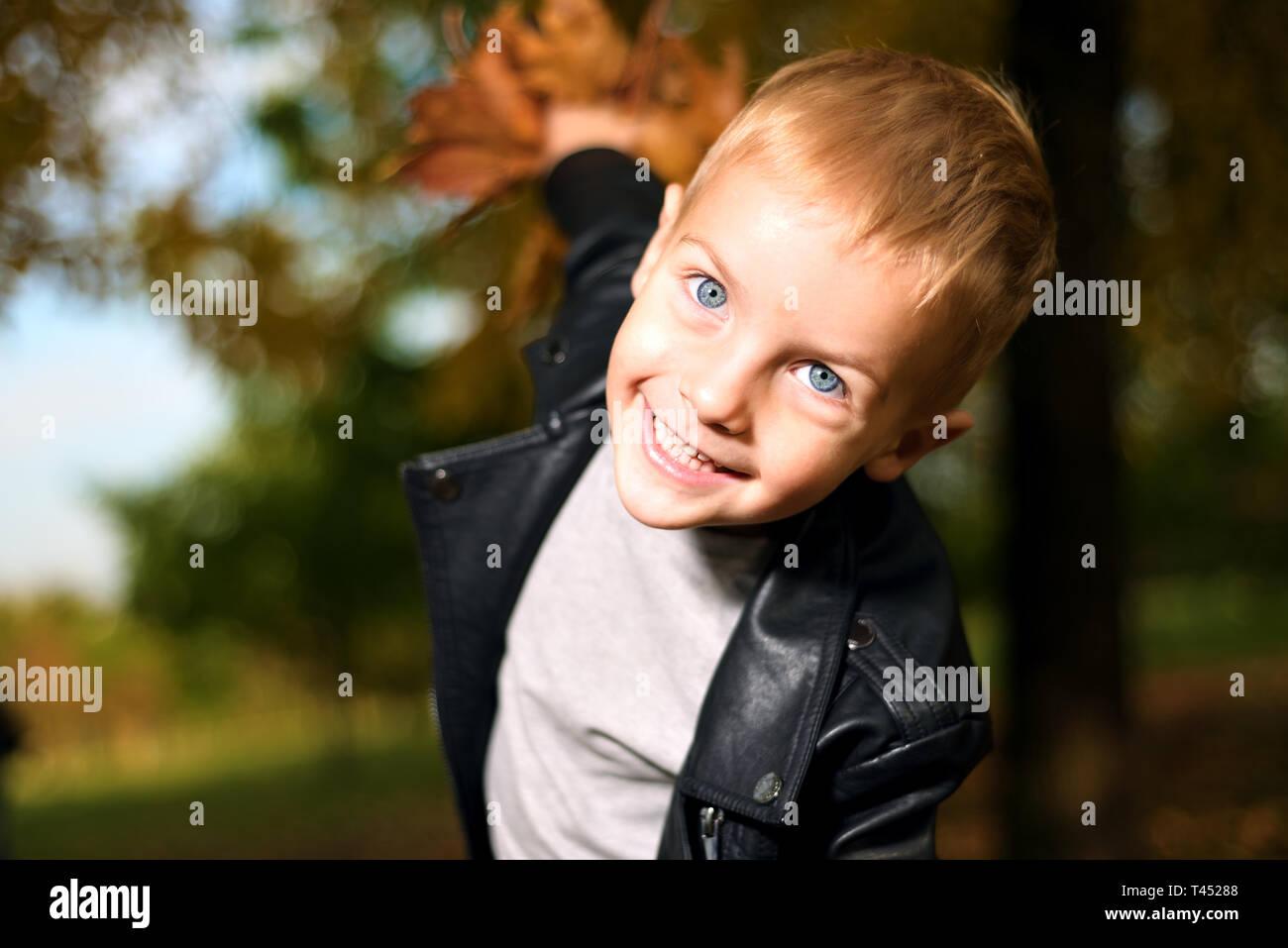 Funny portrait of little boy sly en veste en cuir noire saison d'automne. Banque D'Images