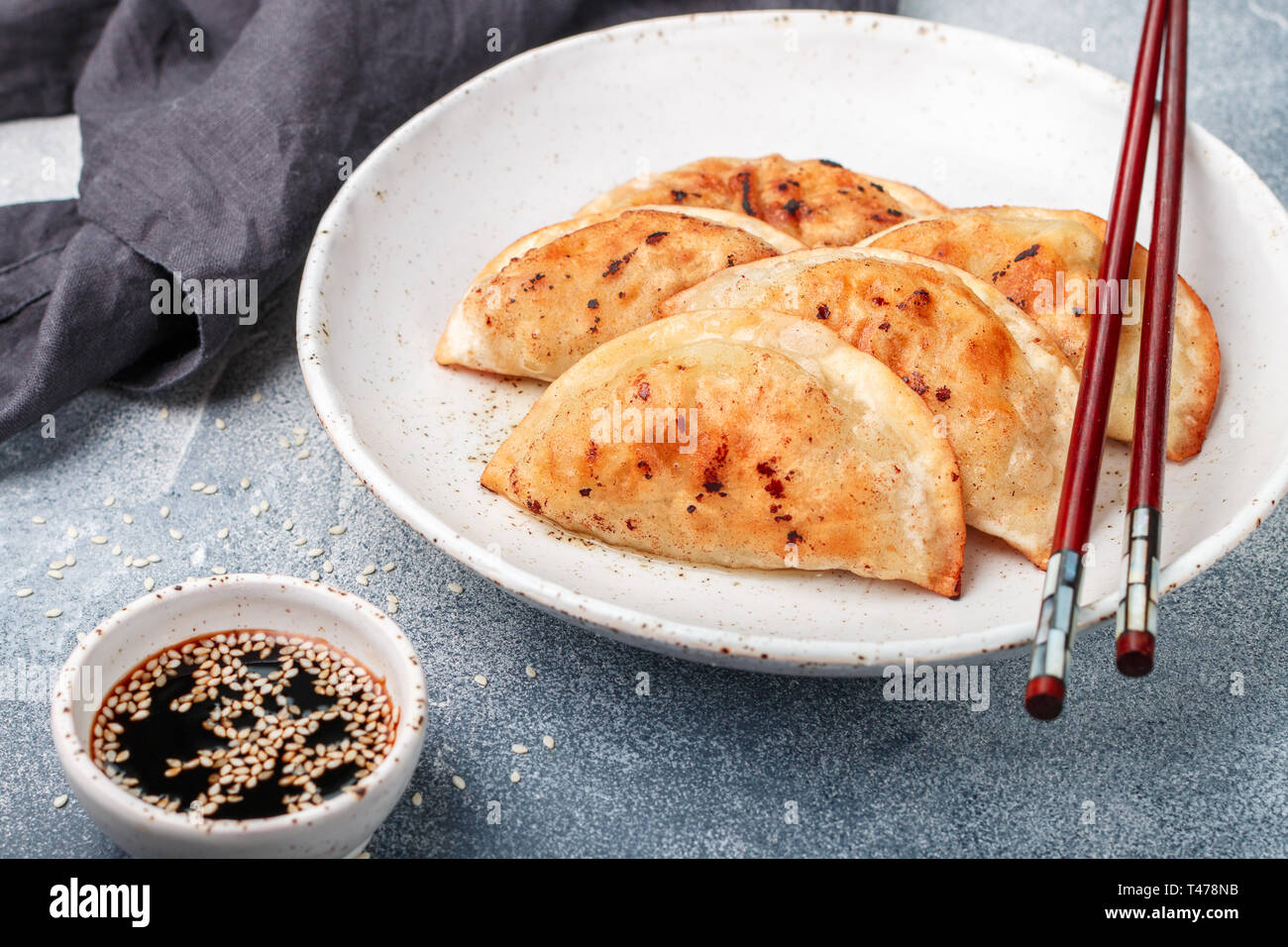 Boulettes frites avec de la viande (boeuf, porc) ou de fruits de mer, le chou et les épices dans une assiette blanche avec de la sauce soja et de graines de sésame. Cuisine asiatique traditionnelle. Le J Banque D'Images